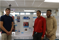 "Bellport High School seniors Peter Mistretta, Chrissy Hobson and Adrian Trent show off their marketing skills for a virtual enterprise called ""Portside Sweets"" during a CTE Month presentation last week."