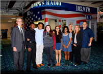 Pictured Left to right: Mr. Tim Hogan (Principal), Students Patrick Ferrell, Marquis Steward, Caitlynn Boogertman, Erin Berja, Nia Tucker, Mrs. Sheila Smith (Business Teacher), Mrs. Erika Della Rosa (Assistant Principal), Mr. Robert Vecchio (LI News Radio).
